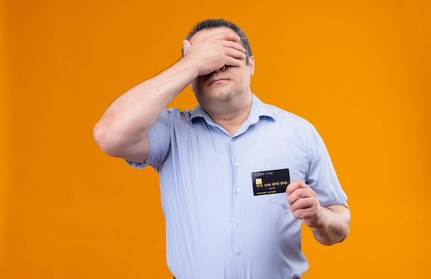 Verwirrter und gestresster mann mittleren alters im blau gestreiften hemd, das kreditkarte hält, während augen mit hand bedeckt