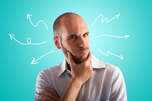 Verwirrter und nachdenklicher mann denkt über den besten weg nach vorne nach