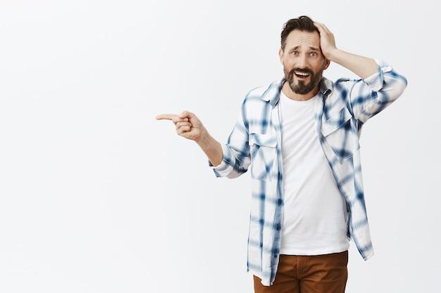 Verwirrter und schockierter bärtiger reifer mann posiert