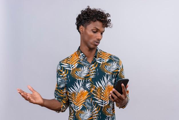 Verwirrter und überraschter junger gutaussehender dunkelhäutiger mann mit lockigem haar, der ein mobiltelefon hält, das zweifel hat, während er hand hebt