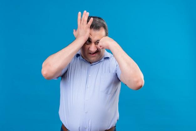 Verwirrter und verärgerter mann mittleren alters im blauen vertikal gestreiften hemd, das hand auf stirn auf einem blauen raum hält