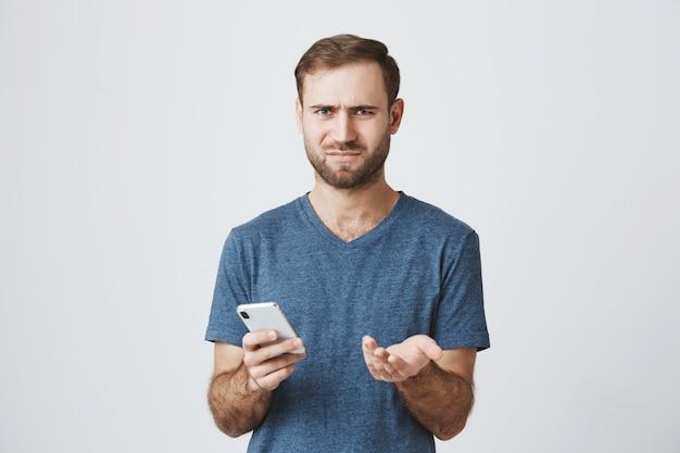 Verwirrter und verwirrter mann zuckt die achseln, nachdem er die nachricht am telefon gelesen hat