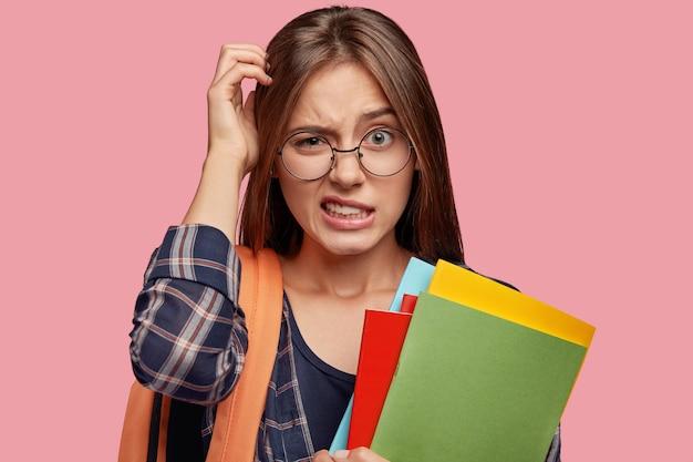 Verwirrter unsicherer student, der mit brille gegen die rosa wand posiert