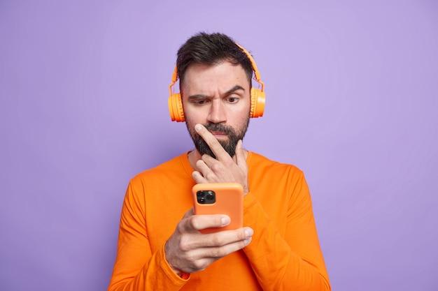 Verwirrter, unzufriedener mann schaut aufmerksam auf das smartphone-display, verwendet das mobiltelefon, um nachrichten online zu überprüfen, trägt kopfhörer auf den ohren und stellt sich allein gegen die violette wand. lifestyle-technologie