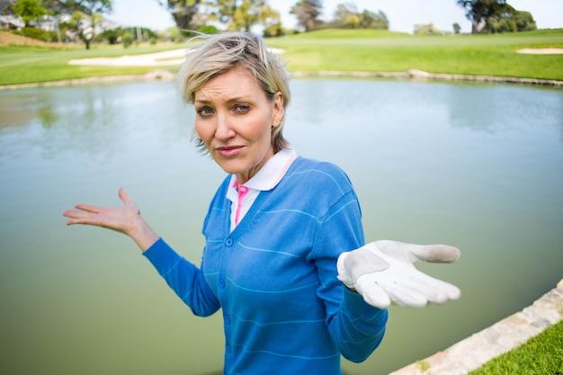 Verwirrter weiblicher golfspieler, der see betrachtet