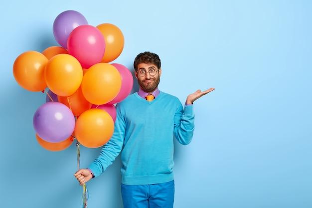 Verwirrter zögernder kerl mit luftballons, die im blauen pullover aufwerfen
