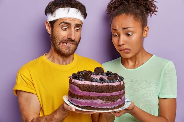 Verwirrtes aktives paar, das mit einem großen kuchen aufwirft