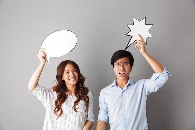 Verwirrtes asiatisches paar, das isoliert steht, leere sprechblase hält, einen streit hat