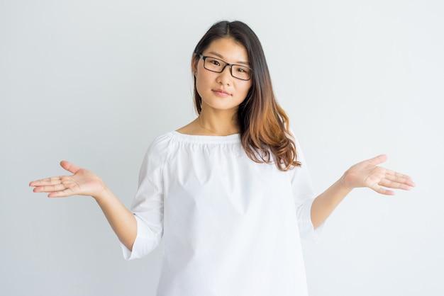 Verwirrtes chinesisches studentenmädchen, das schultern zuckt und kamera betrachtet.