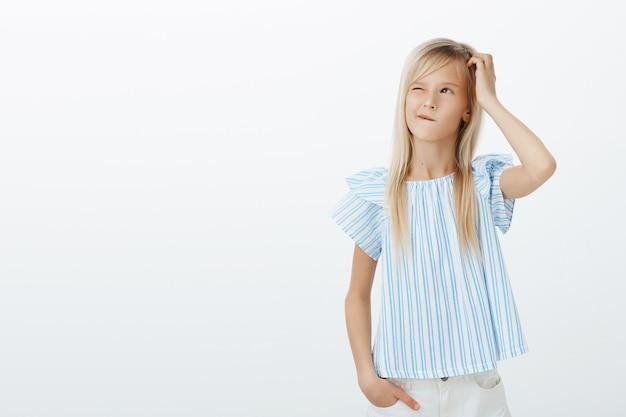 Verwirrtes entzückendes kleines europäisches mädchen in blauer bluse, kratzt sich am kopf und schaut mit leichtem grinsen auf, ist verwirrt und befragt, überlegt, was man tun soll, um spaß zu haben, beunruhigt über graue wand