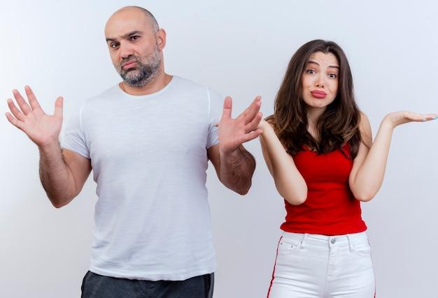 Verwirrtes erwachsenes paar, das beide leere hände zeigt und auf weißer wand isoliert ist