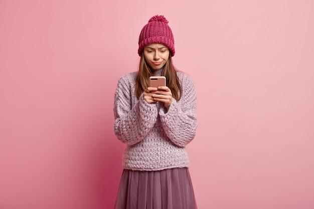 Verwirrtes frustriertes weibliches model, das sich auf das handy konzentriert, seltsame nachrichten liest, im internet surft und modische winterkleidung trägt
