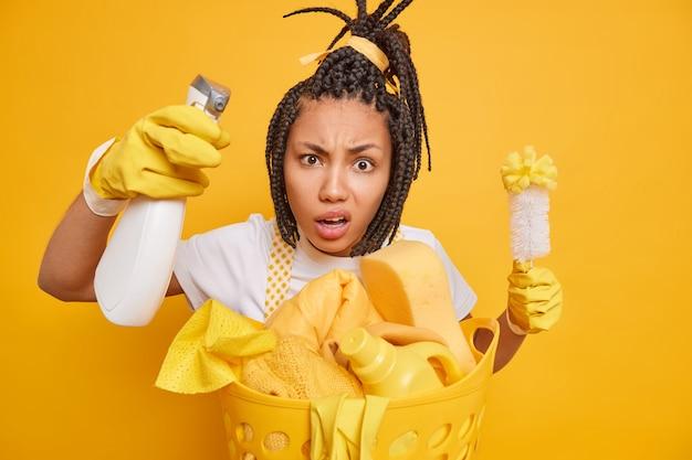 Verwirrtes hausmädchen schaut aufmerksam auf kamerasprays reinigungsmittel wäscht schmutzige oberfläche. halten sie die bürste beschäftigt, die hausaufgaben macht, trägt gummihandschuhe einzeln auf gelbem hintergrund. hygiene-reinigungskonzept