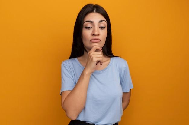 Verwirrtes hübsches brünettes kaukasisches mädchen hält kinn und schaut auf orange herab