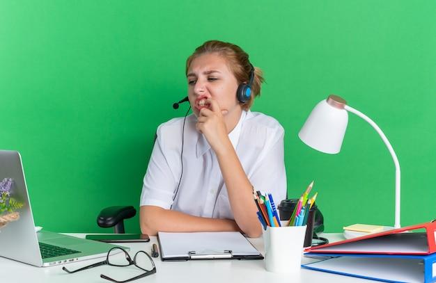 Verwirrtes junges blondes call-center-mädchen mit headset am schreibtisch sitzend mit arbeitswerkzeugen, die den zahn mit dem finger berühren, der auf den laptop schaut