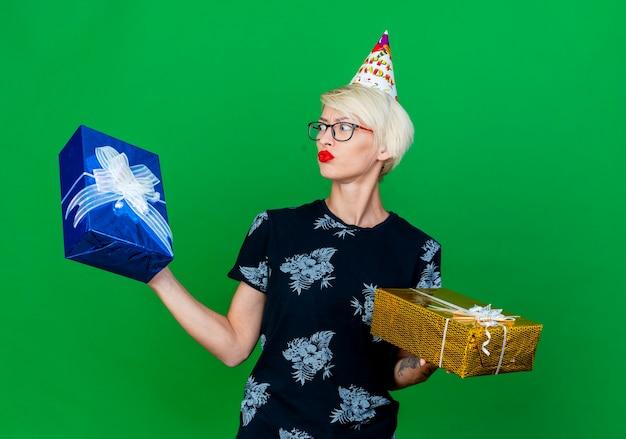 Verwirrtes junges blondes parteimädchen, das brille und geburtstagskappe hält, die geschenkboxen hält, die einen von ihnen lokalisiert auf grünem hintergrund betrachten
