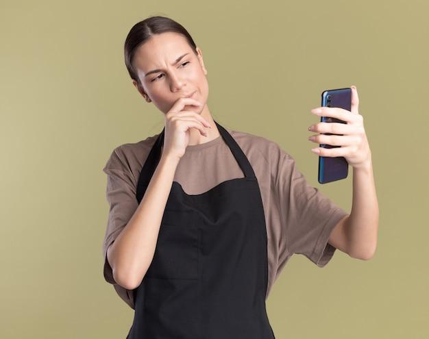 Verwirrtes junges brünettes friseurmädchen in der uniform legt hand auf kinn, das telefon auf olivgrün hält und betrachtet