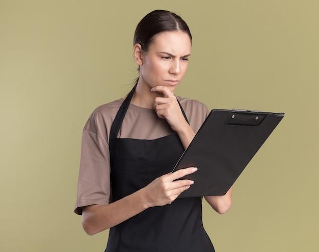 Verwirrtes junges brünettes friseurmädchen in uniform legt die hand auf das kinn und betrachtet die zwischenablage einzeln auf olivgrüner wand mit kopierraum