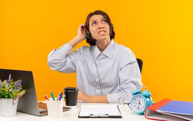Verwirrtes junges callcenter-mädchen, das ein headset trägt, das am schreibtisch sitzt und hand auf den kopf setzt, der lokal auf orange schaut