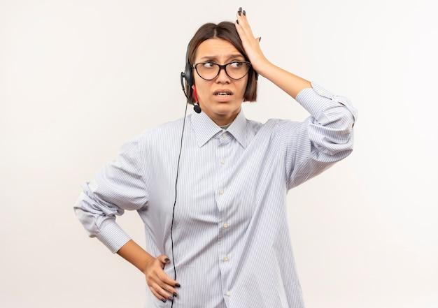 Verwirrtes junges callcenter-mädchen, das eine brille und ein headset trägt, die hände auf kopf und auf taille setzen und die seite lokalisiert auf weiß betrachten
