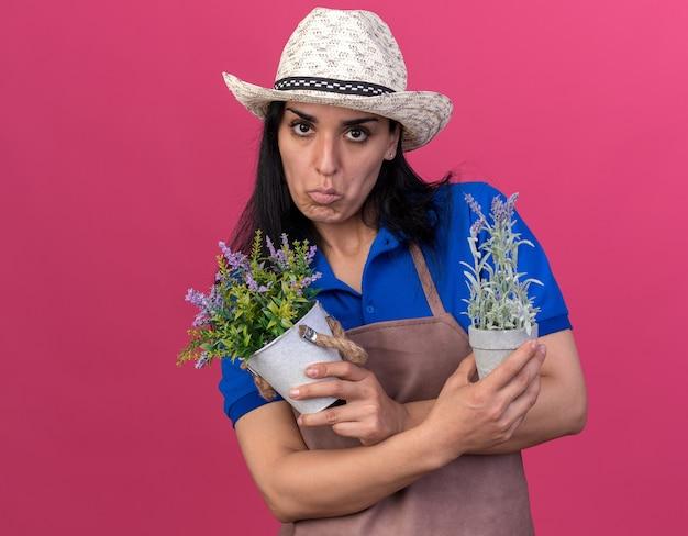 Verwirrtes junges gärtnermädchen in uniform und hut, das blumentöpfe hält, die nach vorne isoliert auf rosa wand mit kopierraum schauen
