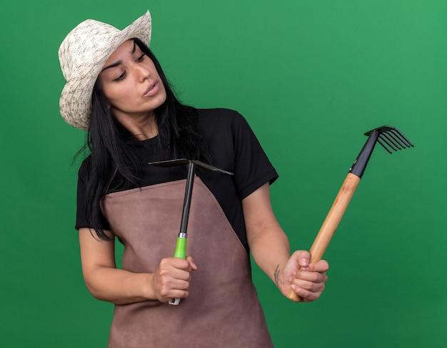 Verwirrtes junges gärtnermädchen in uniform und hut mit rechen und hacke, das auf der grünen wand isoliert auf den rechen schaut