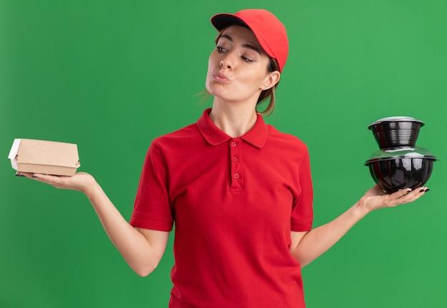 Verwirrtes junges hübsches liefermädchen in uniform hält lebensmittelbehälter und lebensmittelverpackung auf grün