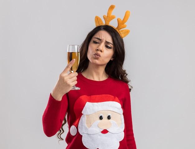 Verwirrtes junges hübsches mädchen, das rentiergeweih-stirnband und weihnachtsmannpullover trägt, der glas champagner mit gespitzten lippen hält und betrachtet