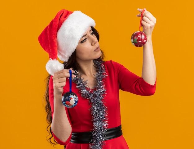 Verwirrtes junges hübsches mädchen, das weihnachtsmütze und lametta-girlande um den hals trägt, der weihnachtskugeln hält, die einen von ihnen lokalisiert auf orangefarbenem hintergrund betrachten