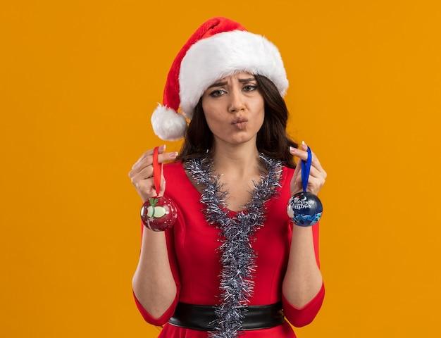 Verwirrtes junges hübsches mädchen mit weihnachtsmütze und lametta-girlande um den hals, das weihnachtskugeln hält, die die lippen einzeln auf oranger wand mit kopienraum schürzen