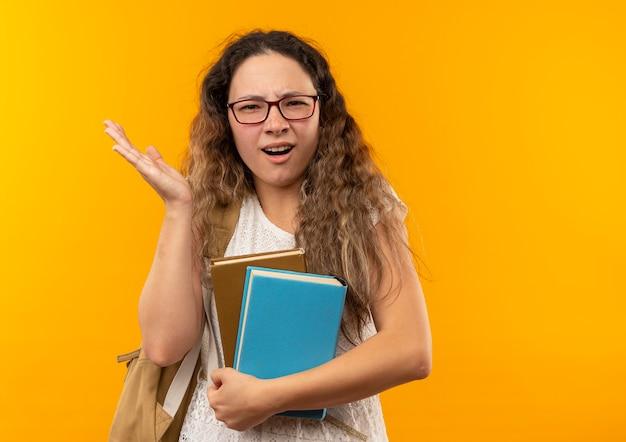 Verwirrtes junges hübsches schulmädchen, das brille und rückentasche hält bücher hält, die leere hand lokalisiert auf gelb mit kopienraum zeigen