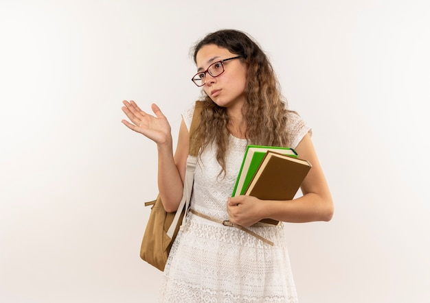 Verwirrtes junges hübsches schulmädchen, das brille und rückentasche hält bücher hält, die leere hand zeigen, die seite lokal auf weiß mit kopienraum betrachtet