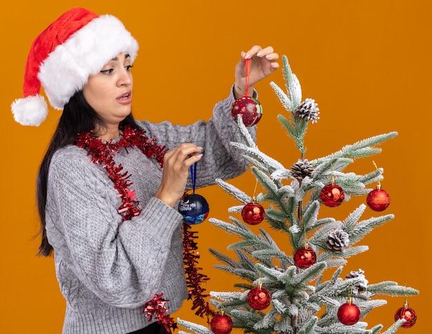 Verwirrtes junges kaukasisches mädchen mit weihnachtsmütze und lametta-girlande um den hals, das in der profilansicht in der nähe des weihnachtsbaums steht und ihn mit weihnachtskugeln schmückt, die sie einzeln auf oranger wand betrachten