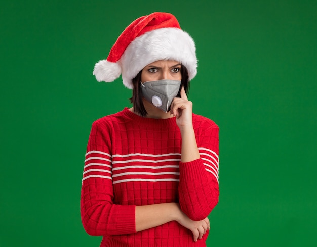 Verwirrtes junges mädchen mit weihnachtsmütze und schutzmaske, das auf die seite schaut und die denkgeste einzeln auf grünem hintergrund mit kopienraum macht