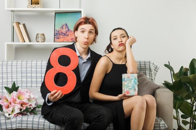 Verwirrtes junges paar am glücklichen frauentag, der die nummer acht hält, während das anwesende mädchen die hand auf die wange legt, die auf dem sofa im wohnzimmer sitzt?
