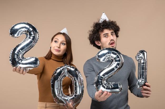 Verwirrtes junges paar tragen neujahrshut posiert für kamera mädchen zeigt und und kerl mit und auf grau