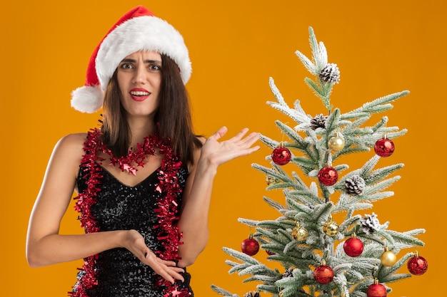 Verwirrtes junges schönes mädchen, das weihnachtsmütze mit girlande am hals trägt, der nahe weihnachtsbaumpunkte mit händen am baum lokalisiert auf orange hintergrund steht