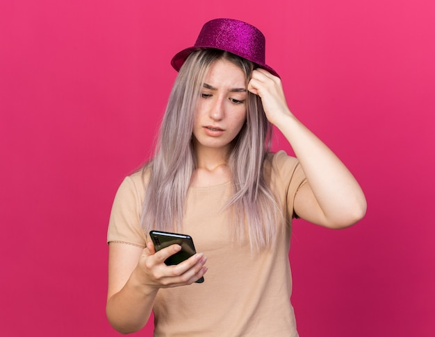 Verwirrtes junges schönes mädchen mit partyhut, das das telefon hält und anschaut und die hand auf die stirn legt