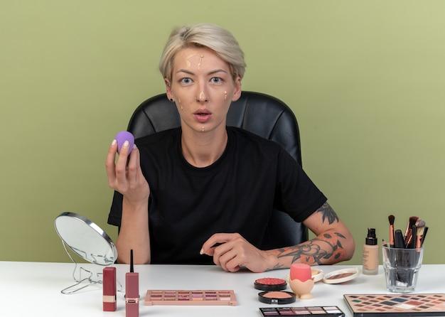 Verwirrtes junges schönes mädchen sitzt am tisch mit make-up-tools, die ton-up-creme mit schwamm auf olivgrüner wand auftragen