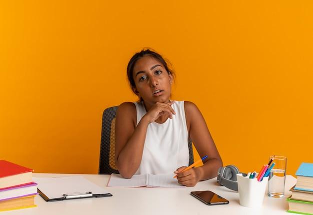 Verwirrtes junges schulmädchen, das am schreibtisch mit schulwerkzeugen sitzt, die stift halten und hand unter kinn legen