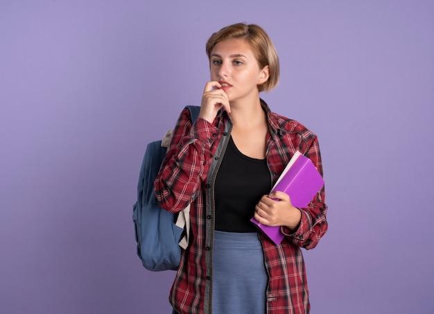 Verwirrtes junges slawisches studentenmädchen, das rucksack trägt, beißt nagel hält buch und notizbuch