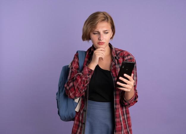 Verwirrtes junges slawisches studentenmädchen, das rucksack trägt, legt hand auf kinngriffe und schaut auf telefon