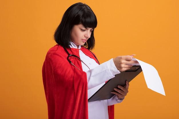 Verwirrtes junges superheldenmädchen, das stethoskop mit medizinischem gewand und umhang trägt, der durch zwischenablage flippt