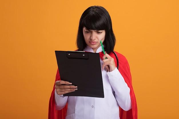Verwirrtes junges superheldenmädchen, das stethoskop mit medizinischem gewand und umhang trägt, hält und betrachtet klemmbrett, das bleistift auf wange setzt