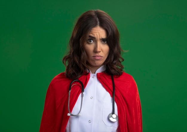 Verwirrtes kaukasisches superheldenmädchen in der arztuniform mit rotem umhang und stethoskop betrachtet kamera