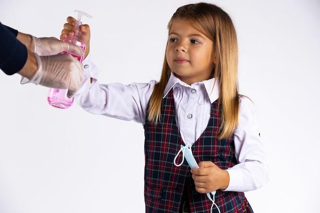 Verwirrtes kleines mädchen mit medizinischer maske in der hand und schuluniform versuchen, das desinfektionsmittel zu nehmen