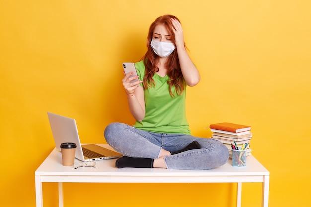 Verwirrtes mädchen mit roten haaren, das auf dem tisch mit dem telefon in den händen sitzt, die schockierende nachrichten im sozialen netzwerk lesen und hand auf kopf halten