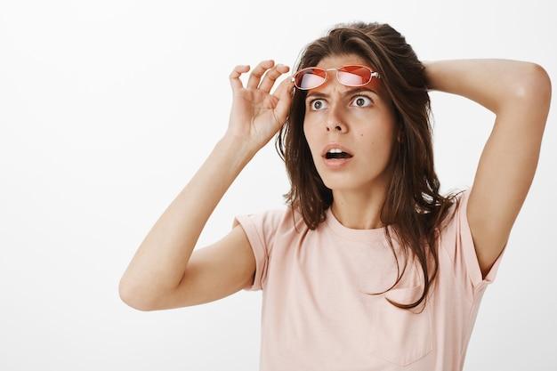 Verwirrtes mädchen mit sonnenbrille, die gegen die weiße wand aufwirft