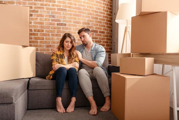 Verwirrtes paar, das umziehen und alle pakete zu neuem zuhause arrangieren muss