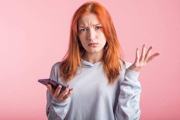 Verwirrtes rothaariges mädchen mit telefon im studio auf rosa hintergrund